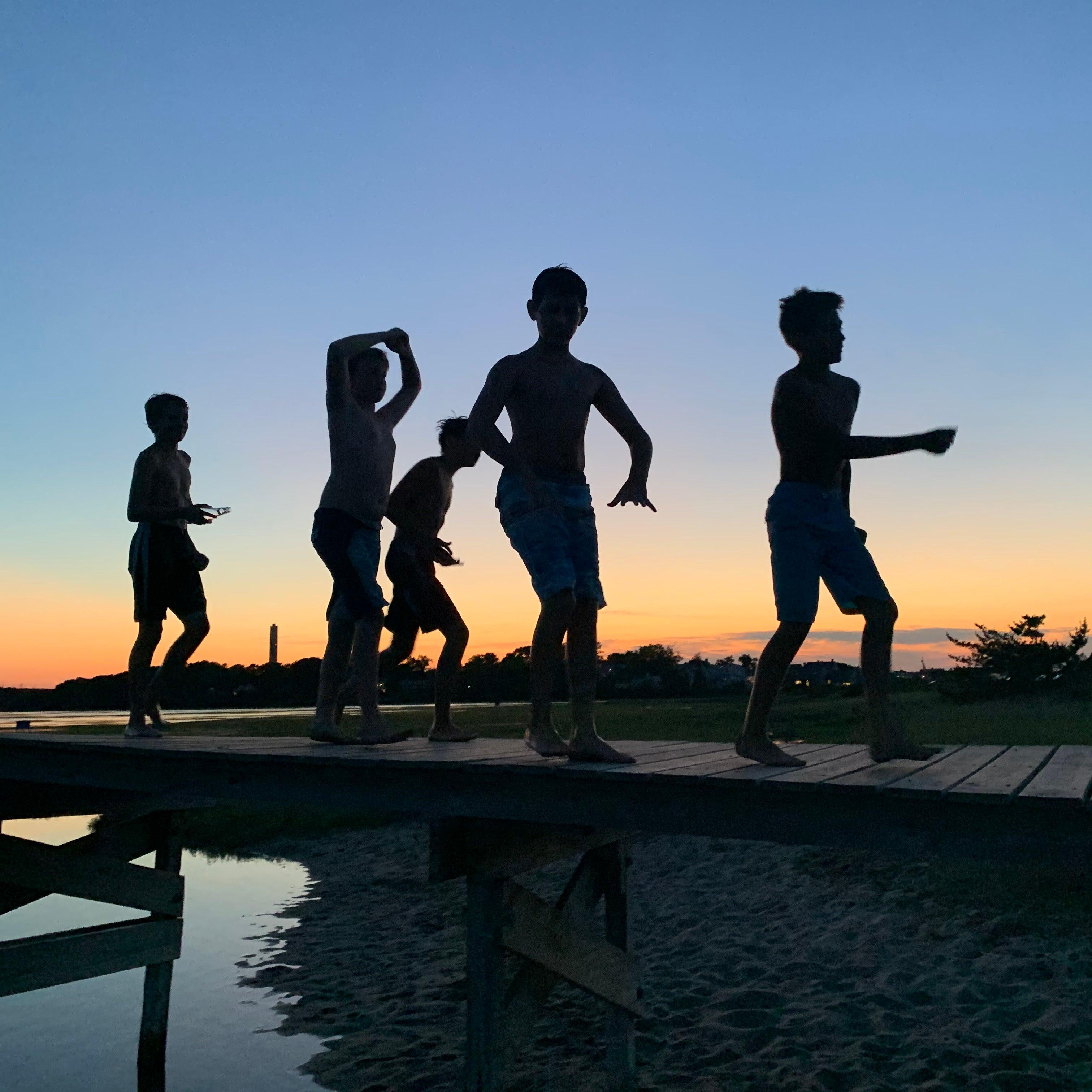 Boys on a boardwalk at sunset in Sandwich
